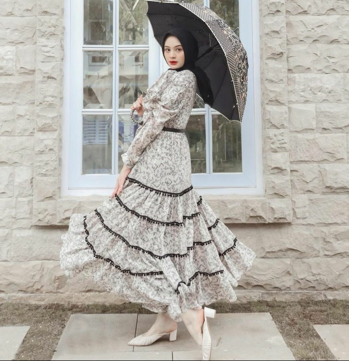 Sabrina berpose anggun nan berkelas menggunakan tiered dress bermotif karya Barli Asmara, dengan cutting puff sleeves dan aksen pom pom pada bagian bawah dress. Pemilihan properti payung menambah kesan romantis. (Foto: Instagram/sabrinasosiawan)