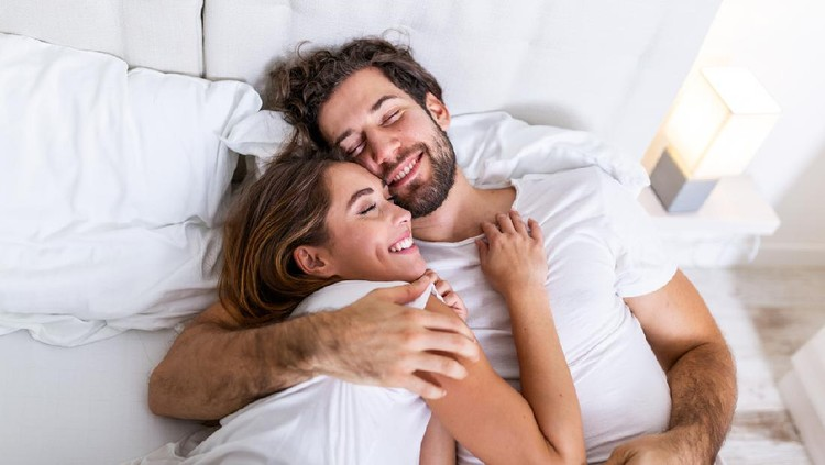 Beautiful loving couple kissing in bed. beautiful young couple lying together on the bed. Romantic young couple in love lying on bed. Beautiful couple smiling in bed.