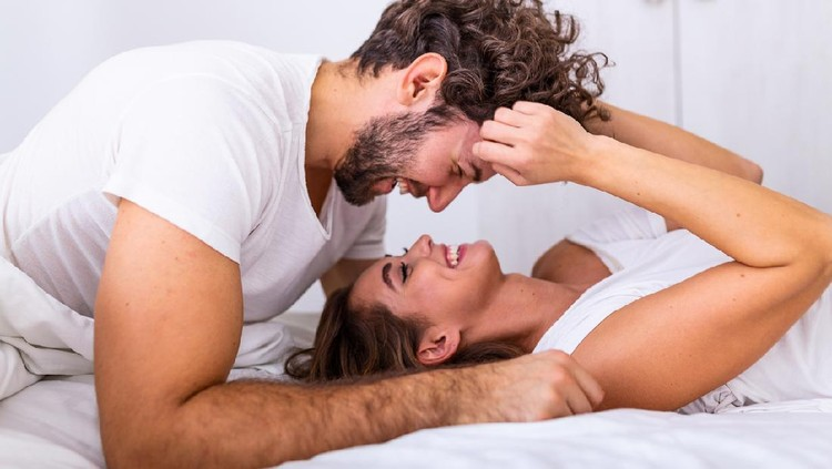 Affectionate young attractive couple sharing a romantic moment in the bedroom at home. Happy young couple hugging and smiling while lying on the bed in a bedroom at home.