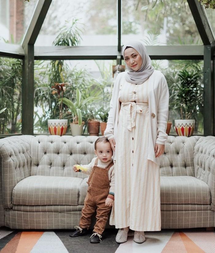 Kalau kamu suka yang kalem-kalem, dress ini cocok juga masuk daftar contekan! Detail vertikal cream yang senada dengan outer sangat pas disandingkan hijab abu-abu. Meski sederhana outfit putihmu tetap nggak mengecewakan. (Foto: instagram.com/rachelvennya)