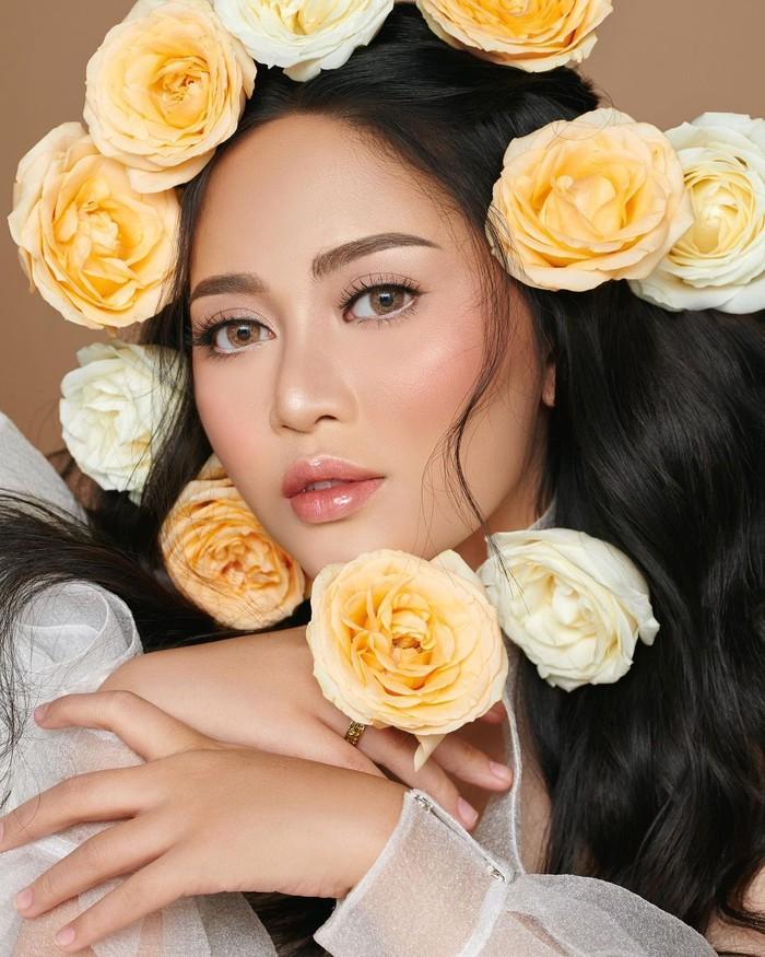 Masih dalam pemotretan yang sama, kali ini sang influencer berpose dengan dikelilingi bunga mawar. Ia tampak menawan dengan makeup bernuansa peach yang flawless dan memberi kesan fresh. Lengkap dengan polesan alis yang tegas dan ombre lips. (Foto: instagram.com/rachelvennya)
