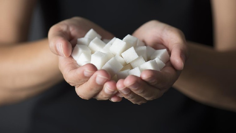 Caucasian female is holding sugar cubes in hand.