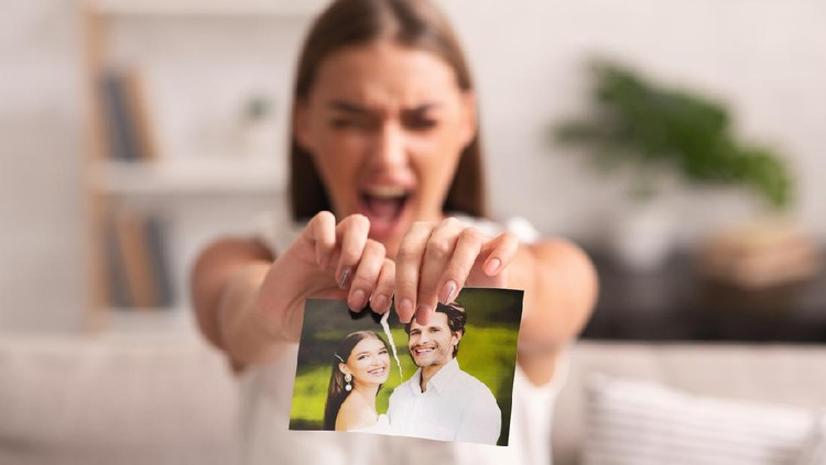 Breakup. Furious Woman Ripping Wedding Photo With Ex-Husband Sitting On Sofa Indoor After Divorce. Selective Focus