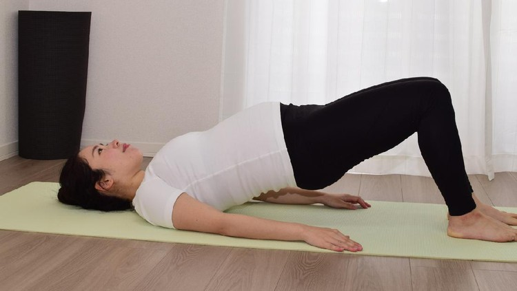 A young pregnant woman is doing fitness at home. It is important to exercise during pregnancy.