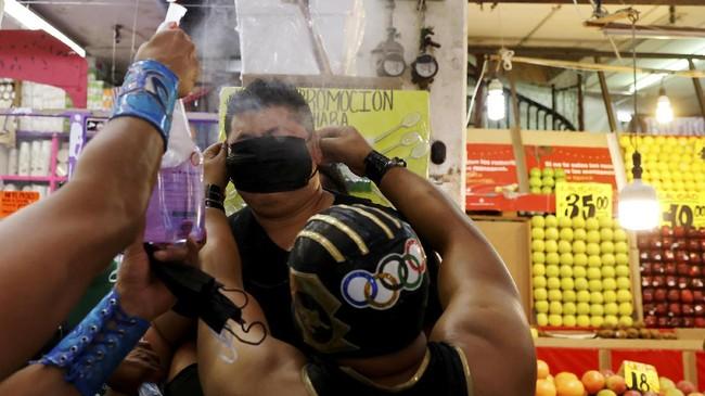 Sekelompok pegulat gaya bebas lucha libre Meksiko mengampiri pasar grosir makanan terbesar untuk merazia warga yang keluar rumah tidak memakai masker.
