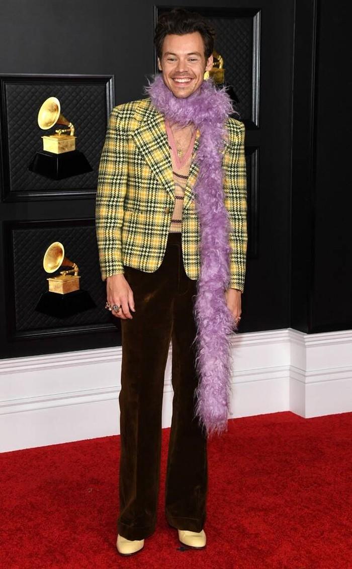 Harry Style hadir dengan penampilan yang terinspirasi dari fesyen era 90-an dalam red carpet kali ini dari koleksi Gucci. Dia memakai blazer motif kotak kuning-coklat, celana coklat dengan poin boa (selendang bulu) warna lilac/Sumber/E Online.