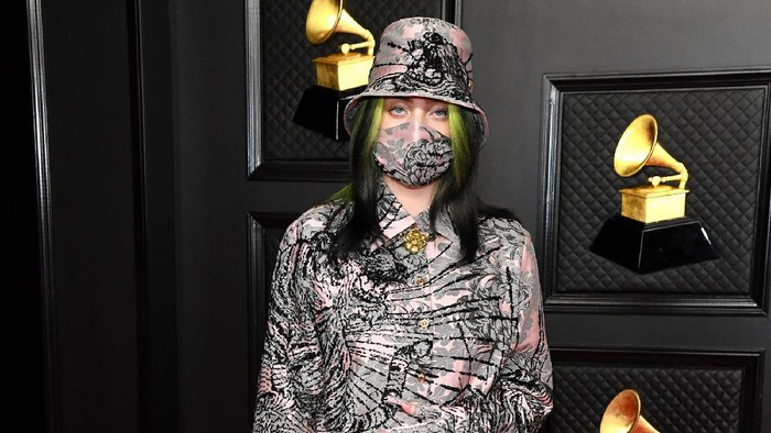 Billie Eilish mempercayakan Gucci untuk pakaiannya saat menghadiri Grammy Awards. Pelantun Everything I Wanted ini memakai setelan atasan dan celana warna pink-gray lengkap dengan bucket hatdan masker./Foto: Page Six