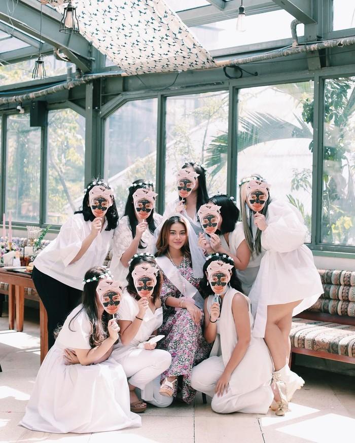 Para sahabat Aurel kompak menggunakan pakaian berwarna putih, mereka juga membawa atribut berupa topeng bergambar wajah Atta Halilintar yang sedang memakai masker (foto: instagram.com/aurelie.hermansyah)