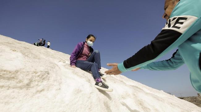 Bukan di gunung es atau di gurun pasir, warga Mesir kini asyik meluncur bebas dari bukit garam.
