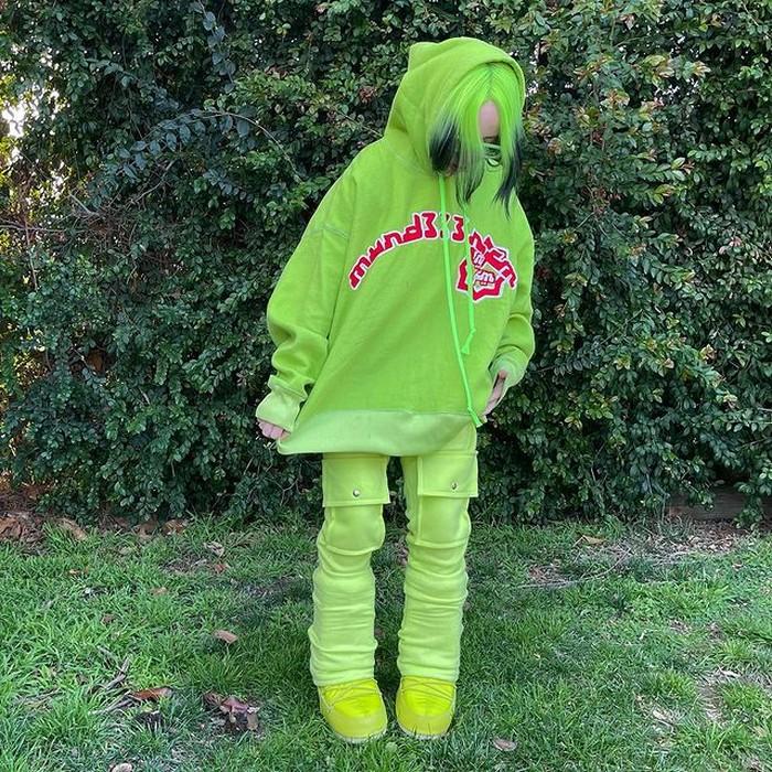 Warna neon sepertinya menjadi ikon khas dari Billie Eilish. Di sini, dirinya memadupadankan hoodie oversizedengan sepatu boots dan celana multi saku dengan warna keseluruhan yang senada. (foto: instagram.com/billieeilish)