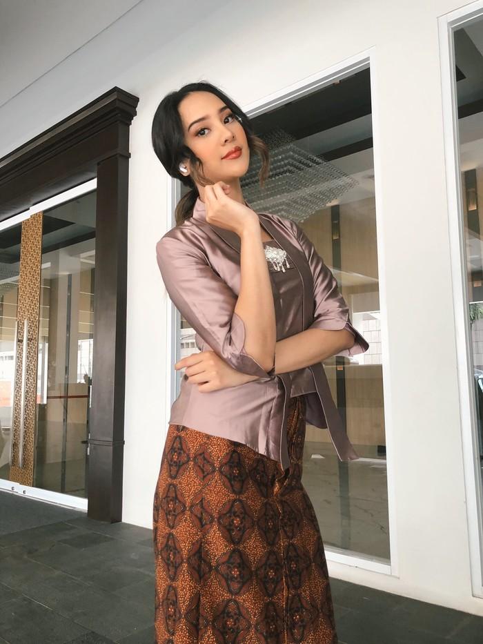 Kali ini Anya mengenakan kebaya satin model kutubaru dipadukan dengan kain batik coklat. Dilengkapi aksesoris bros pada bagian dada, penampilan Anya tetap modis walaupun memakai busana tradisional. (Foto:Instagram.com/anyageraldine)