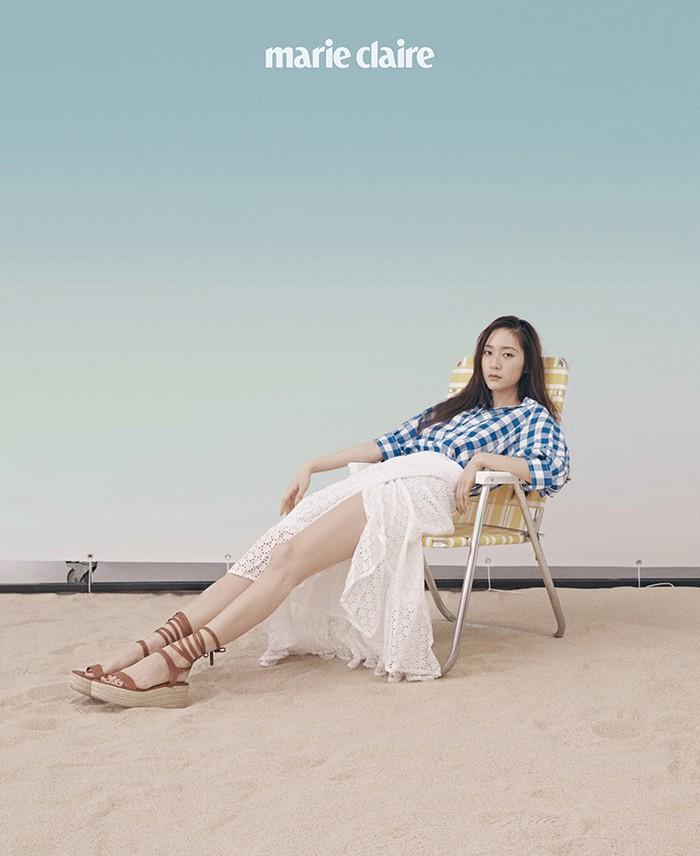 Tampil lebih santai, Krystal menggunakan perpaduan check shirt dan wrap skirt serta wedges cokelat. Look ini semakin memancarkan vibes liburan ya, Ladies! (Foto: marieclairekorea.com)