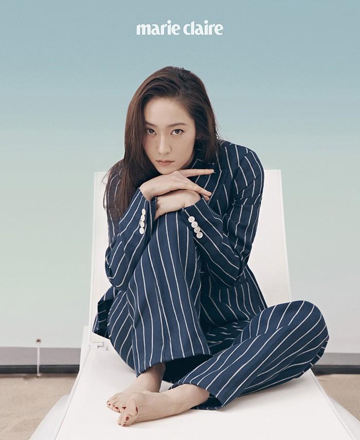 Dengan duduk di atas kursi santai, Krystal berpose menatap kamera dan memakai setelan blazer linen dan celana garis berwarna navy. (Foto: marieclairekorea.com)