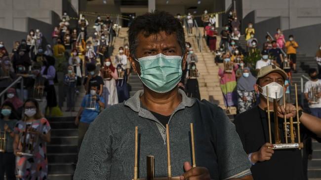 Lebih dari 1.500 pasien dan tenaga kesehatan bermain angklung dalam peringatan setahun beroperasinya RS Darurat Covid-19 Wisma Atlet Kemayoran, Selasa (23/3).