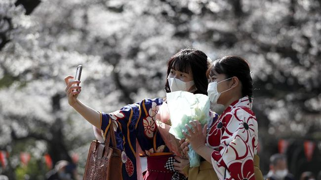 Di tengah pandemi virus Corona, masih banyak penduduk Jepang yang keluar rumah untuk menikmati musim mekar bunga sakura.