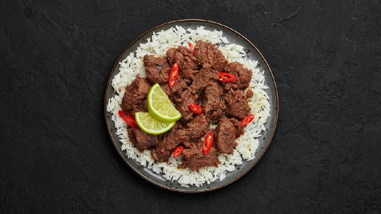 Beef Rendang on black plate at black slate table top. Indonesian padang cuisine meat dish. Asian food. Top view