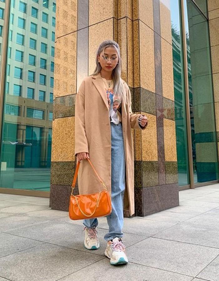 Di sini, gaya streetstyle Dillah tampak lebih mature dengan pemakaian long coat berwarna cokelat ini. Pemakaian handbag oranye dan sneakers putih membuatnya terlihat menawan. (foto: instagram.com/dillaprb)