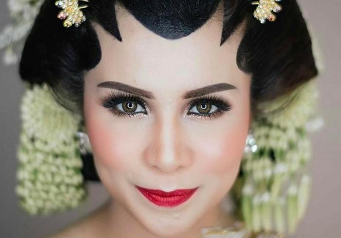 Momo Geisha menampilkan kesan yang glamour untuk makeup pengantin Jawa-nya. Riasan mata bernuansa smoke eyes terlihat lebih dramatis. Semakin lengkap dengan pilihan lipstik merah yang begitu indah. (Foto: instagram.com/therealmomogeisha)