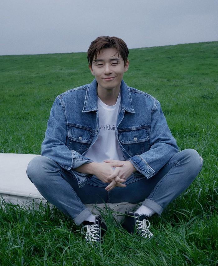 Kali ini, Park Seo Joon tampil keren dengan koleksi kaos putih dari Calvin Klein, jaket jeans, celana jeans, serta memakai sneakers casual. Senyuman dari Park Seo Joon juga membuat tampilannya lebih manis dan memukau. (Foto: instagram.com/dazedkorea)