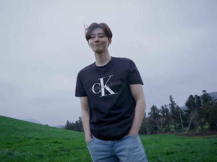 Paduan kaos hitam dari Calvin Klein serta celana jeans berwarna cerah ini juga membuat tampilan Park Seo Joon terlihat lebih santai dan lebih kece, nih! (Foto: instagram.com/dazedkorea)