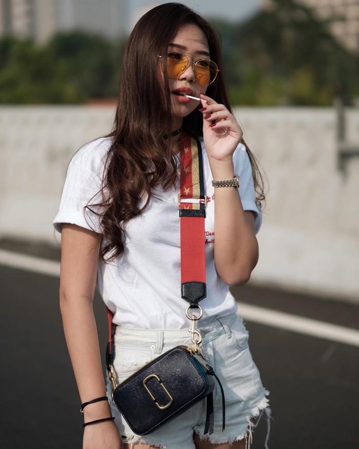 Memadukant-shirtputih lenganpendek putih dengan denim hot pants warna senada bisa jadi inspirasi buat tampil stylish. Kamu juga bisa pilih sling bag warna hitam dengan strape merah untuk memaksimalkan penampilan (Foto: www.instagram.com/siscakohl/).