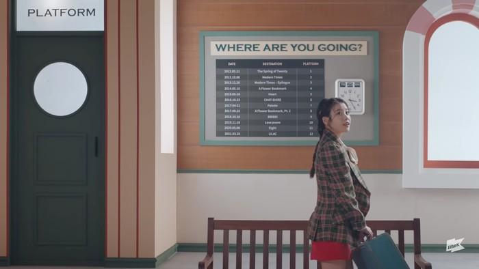 Di awal video, IU tampak memasuki sebuah stasiun kereta untuk melakukan perjalanan. Blazer motif plaid dan mini skirt merah membuat tampilannya terlihat cute. Dandanan rambut yang indah semakin melengkapinya. (Foto:youtube.com/1theK)