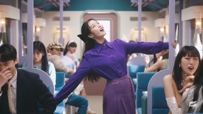 Saat scene memasuki kereta, IU tampil riang gembira dengan tarian menggemaskan. Outfit serba ungu yang dikenakannya tampak relevan dengan judul MV. Nuansa keceriaan seorang IU sangat tampak di sini. (Foto:youtube.com/1theK)