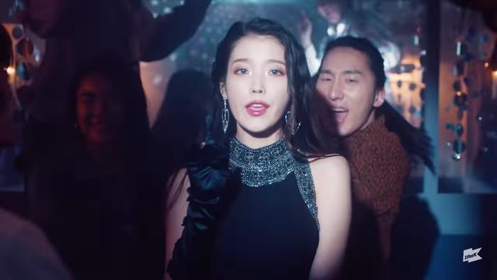IU tampak elegan dengan sleeveless dress warna hitam di scene night party. Ia juga mengenakan kaos tangan hitam yang kece. Dengan rambut yang dibiarkan tergerai, pesona IU tampak sangat memukau. (Foto:youtube.com/1theK)