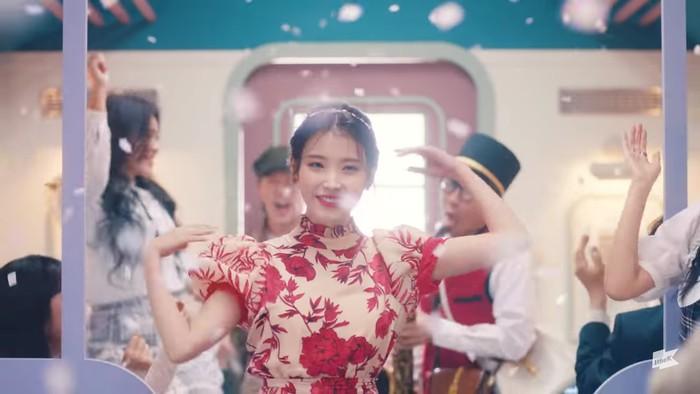 Kembali di suasana gerbong kereta, IU terlihat menari bersama dengan para penumpang. IU memakai dress bermotif floral kombinasi warna merah dan krem. Seyuman manisnya tampak menyempurnakan scene ini. (Foto:youtube.com/1theK)