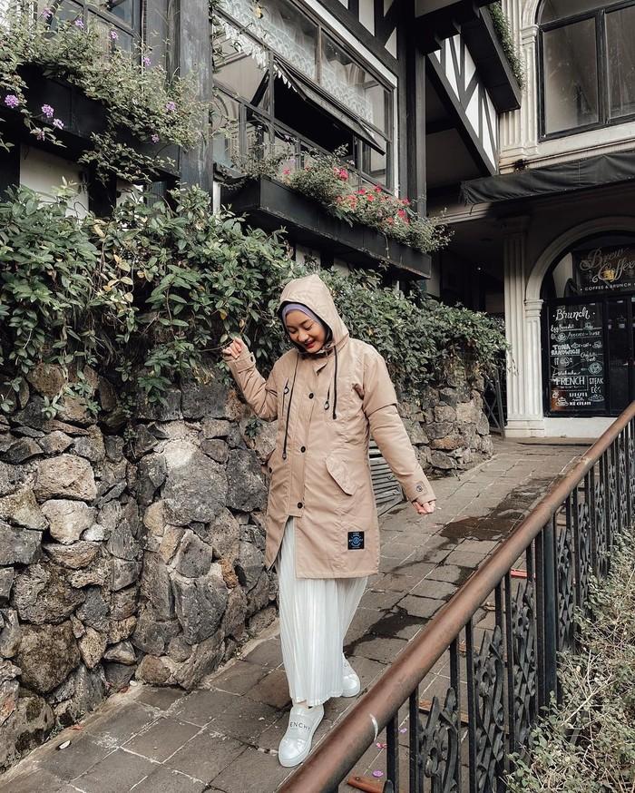 Lewat potret terbaru Dinda Hauw tampil modis dengan outfit bumil warna soft. Kamu bisa menirunya dengan memadukan jaket cokelat muda dan rok plisket putih. Pilih hijab biru dan slip-on sneakers putih untuk tampil modis (Foto: www.instagram.com/dindahw/).