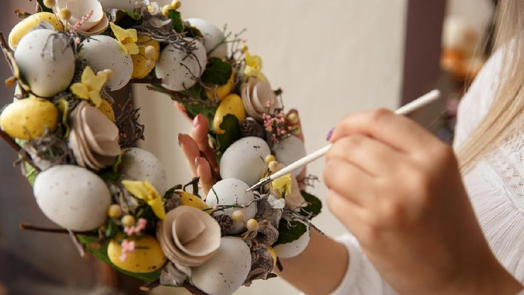 Girl paints on handmade wreath with Easter eggs. Woman draws on easter eggs