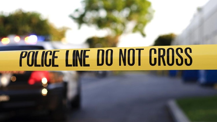 A blurred police car in the background behind yellow crime scene tape.