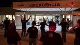 Anggota Gereja dan Pusat Rehabilitasi God's Love Evangelical merapalkan doa untuk pasien Covid-19 dari luar rumah sakit di Rio de Janeiro, Brasil.