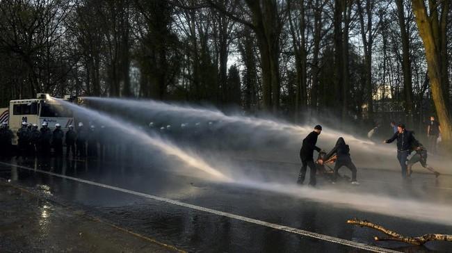 Polisi semprotkan water cannon ke ribuan orang yang berkumpul di taman Brussel untuk menyaksikan konser palsu yang diumumkan di medsos.