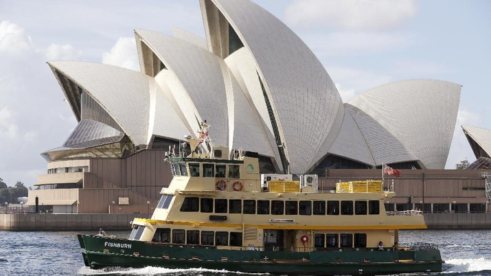 A ferry sails past the Opera House in Sydney, Australia, Tuesday, April 6, 2021. New Zealand announced the start date for a long-anticipated travel bubble between Australia and New Zealand that will allow people to travel between the two countries without going through quarantine, allowing families to reunite and giving a big boost to the struggling tourism industry will begin April 19. (AP Photo/Rick Rycroft)