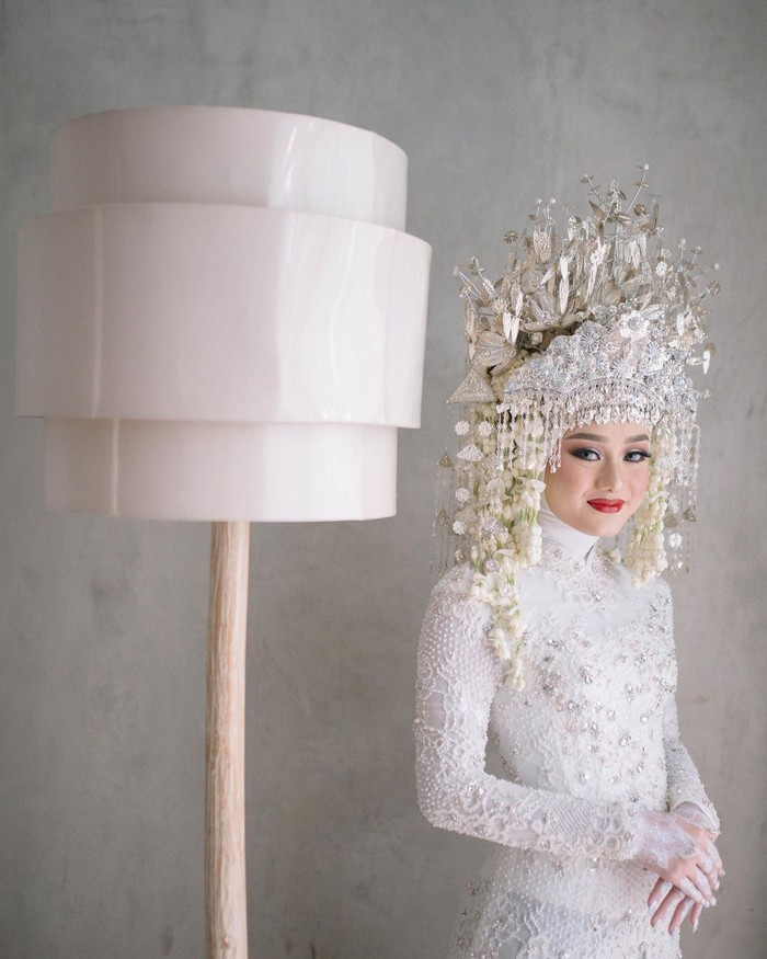 Dinda Hauw tampil cantik dengan kebaya putih berbahan brokat di hari pernikahan. Kebaya putih itu diberi detail beaded warna silver sehingga tampak lebih mewah. Berpadu dengan nuansa adat Palembang, Dinda sangat memesona.(Foto:instagram.com/imagenic)