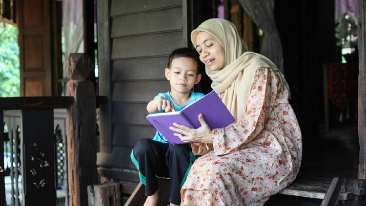 A Malay Muslim mother reading a book with her son on a verandah of a Malay traditional house.