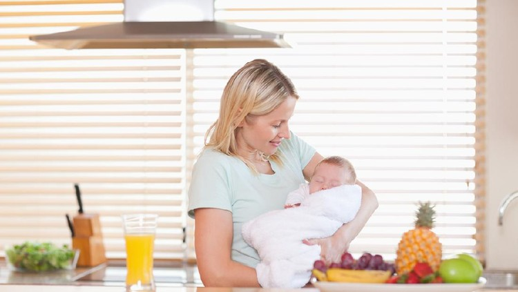 Young woman holding her sleeping baby in the kitchen