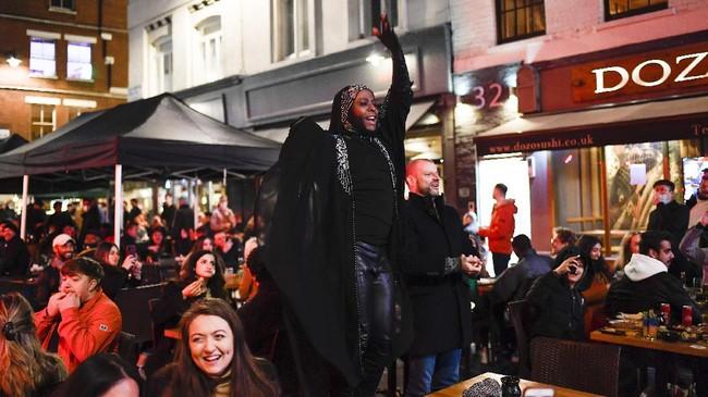 Warga London, Inggris, bersulang alkohol merayakan pembukaan lockdown di tengah pandemi Covid-19.