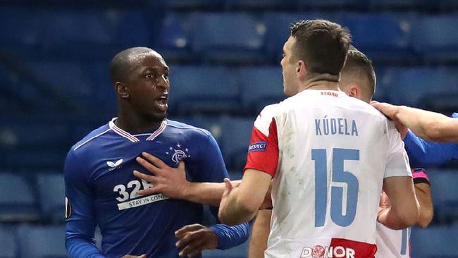 Bek Slavia Praha Ondrej Kudela telah dilarang bermain selama sepuluh pertandingan oleh UEFA karena melakukan pelecehan rasisme terhadap Glen Kamara.