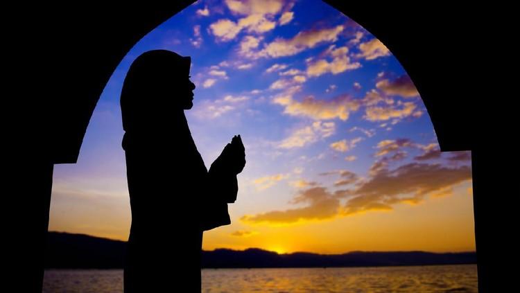 Arab woman with veil against orange yellow sky