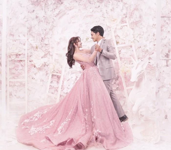 Keduanya tampak berdansa di salah satu shoot prewedding. Layaknya pangeran dan princess, hasil foto yang ditampilkan sangat memikat. Bunga-bunga pink yang dijadikan latar seakan menjadi lambang cinta yang mekar. (Foto: instagram.com/nandaarsynt)