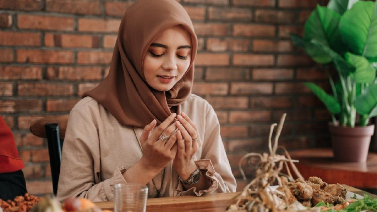 beautiful muslim woman open her palm and pray before eating