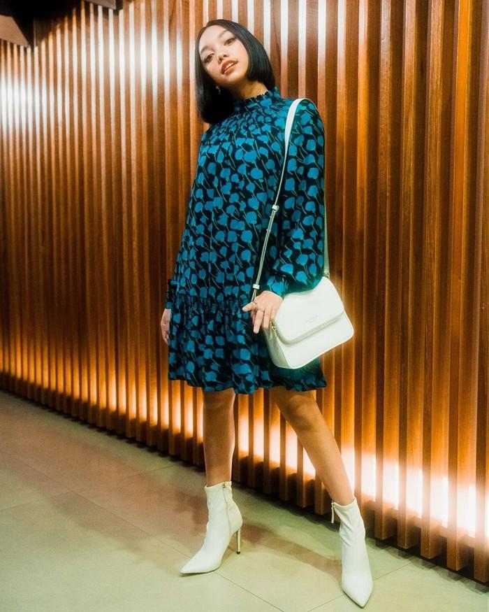 Naura tampil dengan dress klasik becorak dengan long sleeve koleksi Kate Spade New York yang dipadukan dengan boot heels putih yang senada dengan tasnya/Sumber/Instagram/naura.ayu.