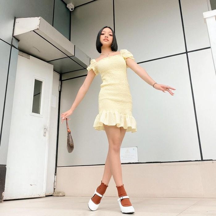 Gadir berusia 15 tahun ini memadukan dress fit body model rample pada bagian ujung lengan dan roknya, dengan high heels. Menariknya, Naura membuat tampilannya lebih manis dengan penambahan kaos kaki/Sumber/Instagram/naura.ayu.