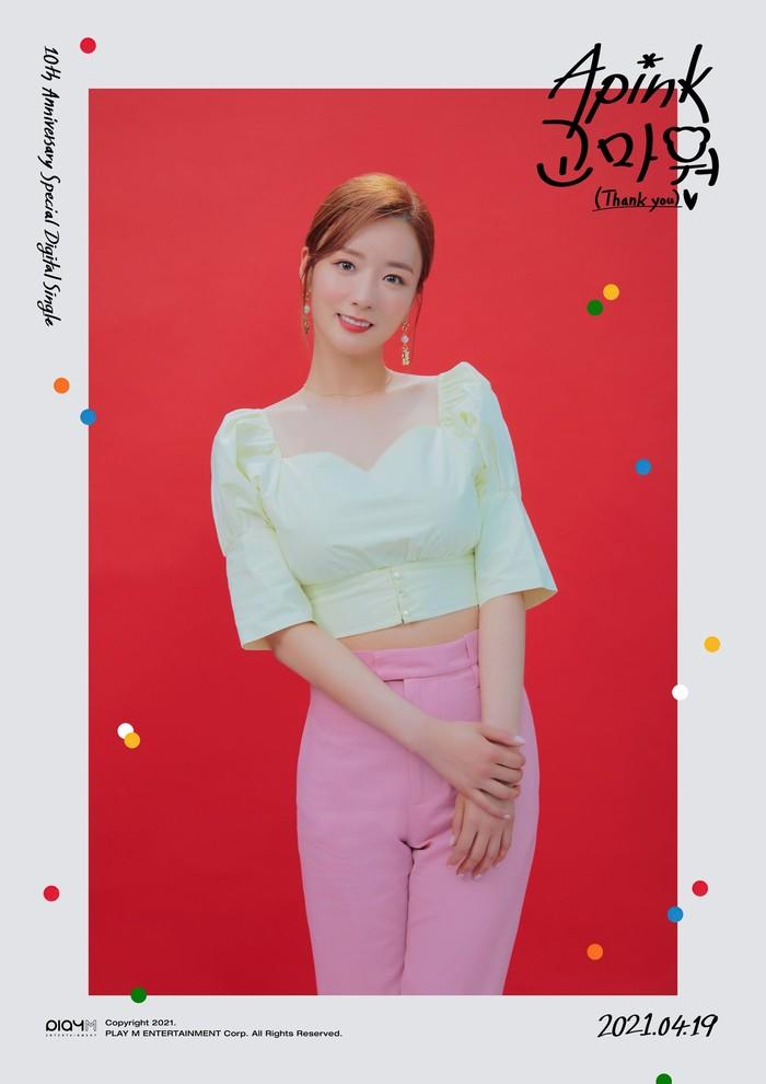 Engga kalah mempesona, ada Bomi yang tampil bagai wanita dewasa dengan atasan crop top light green yang dipasangkan dengan celana pink cerah. Tatanan rambut serta pose sederhana membuatnya semakin elegan. (Foto : Twitter.com/Apink_2011)