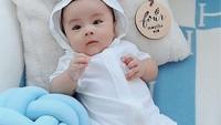 <p>Di lain kesempatan, baby Abe juga turut berpose dengan baju putih lengkap dengan kupluk nih, Bunda. Nuansa biru semakin membuat tampilan baby Abe tampak lucu, ya. (Foto: instagram: @therealmomogeisha)</p>