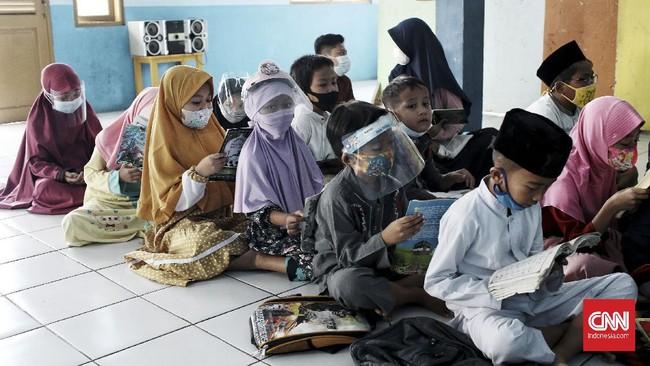 Sembari memakai masker, anak-anak giat menjalani ibadah tadarus Al-Qur'an di bulan suci Ramadan.