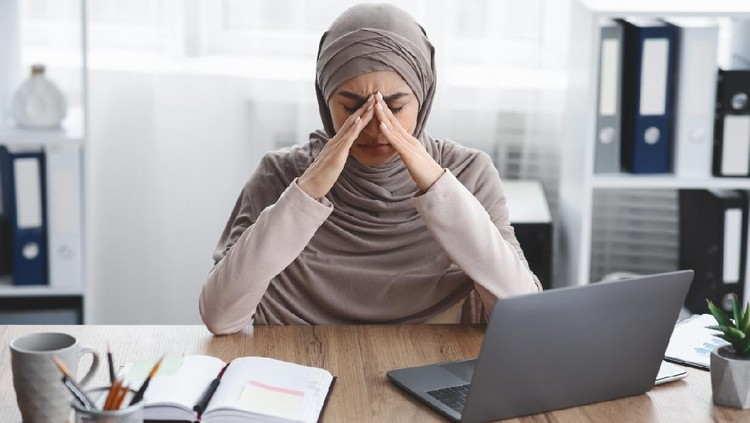 Exhausted arabic businesswoman having migraine after long time work in office, sitting at desk and touching her nose bridge, having bad day