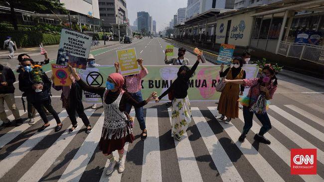 Sejumlah aktivis lingkungan hidup menggelar aksi 'makan' sampah plastik dalam memperingati Hari Bumi 2021 di Kota Surabay, Jawa Timur.